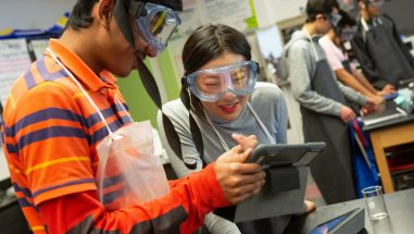 High school students read their lab directions on a computer tablet during AP chemistry class.